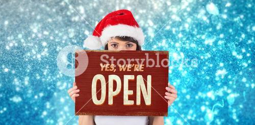 Composite image of pretty santa girl smiling at camera with poster