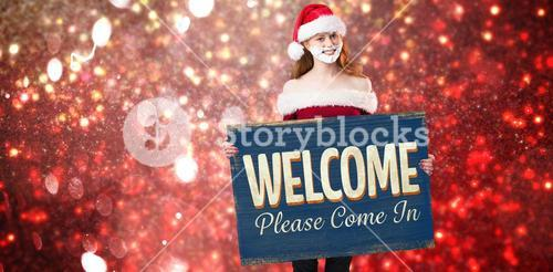 Composite image of festive redhead in foam beard holding poster
