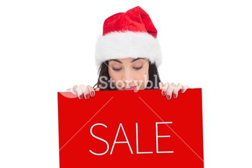 Composite image of pretty brunette in santa hat showing white poster