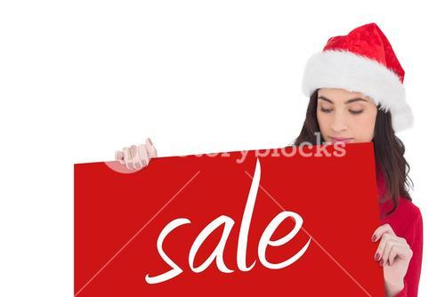 Composite image of beauty brunette in santa hat showing white poster