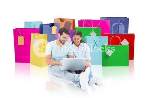 Composite image of cute couple sitting using the laptop