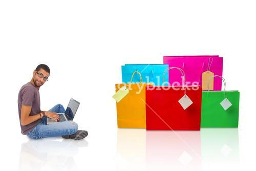 Composite image of man wearing glasses sitting on floor using laptop and looking at camera