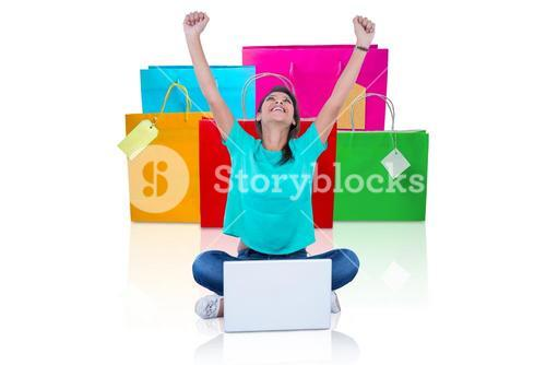 Composite image of woman with arms raised sitting by laptop on white background