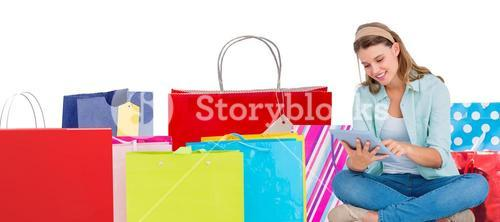 Composite image of pretty hipster using tablet pc