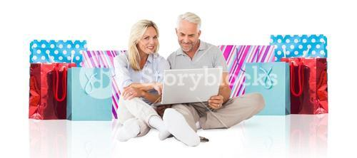 Composite image of cheerful couple using laptop