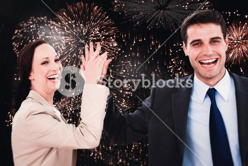Composite image of cheerful workmates doing high five