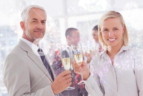Composite image of business team celebrating with champagne and looking at camera