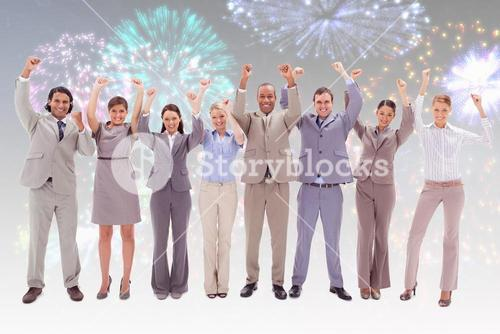 Composite image of happy business team raising their arms