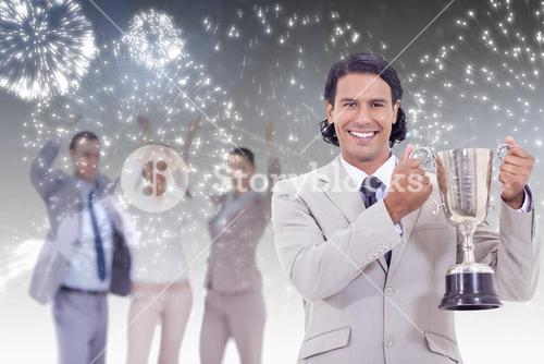 Composite image of close up of a man dressed in a suit smiling and holding a cup with people cheerin