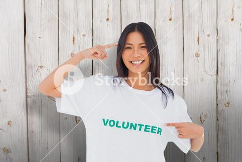 Composite image of smiling woman pointing to her volunteer tshirt