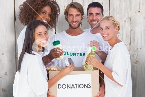 Composite image of happy volunteers putting food in donation box