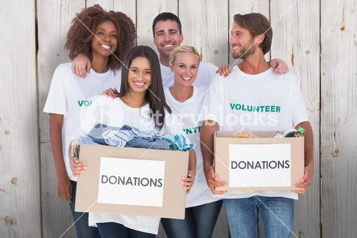 Composite image of happy group of volunteers holding clothes donation boxes