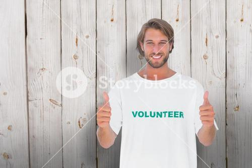 Composite image of happy man wearing volunteer tshirt giving thumbs up