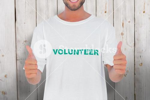 Composite image of man wearing volunteer tshirt giving thumbs up