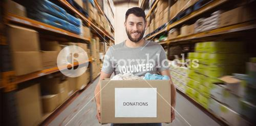 Composite image of portrait of man holding clothes donation box in office