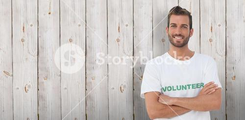 Composite image of portrait of a happy male volunteer with hands crossed