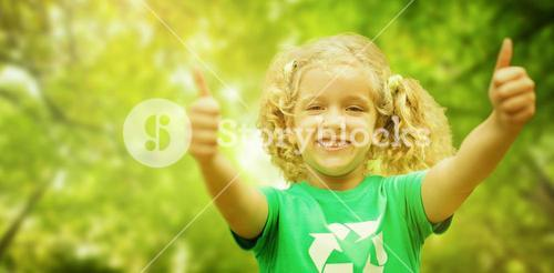 Composite image of happy little girl in green with thumbs up
