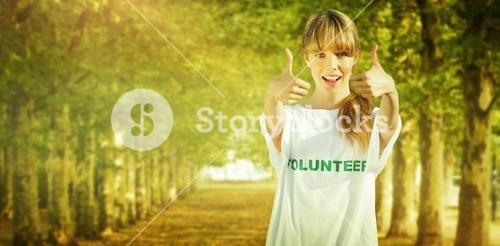 Composite image of natural blonde wearing a volunteering t shirt giving thumbs up