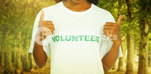 Composite image of woman wearing volunteer tshirt and giving thumbs up