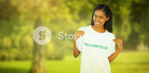 Composite image of young woman wearing volunteer tshirt and pointing to it