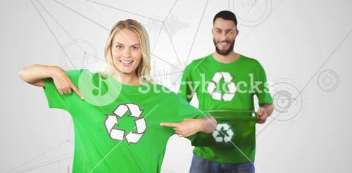 Composite image of portrait of woman pointing towards recycling symbol on tshirts