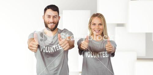 Composite image of smiling volunteers giving thumbs up