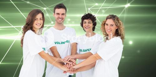 Composite image of smiling volunteer group piling up their hands