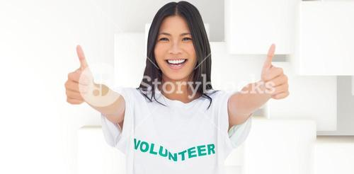 Composite image of woman wearing volunteer tshirt giving thumbs up