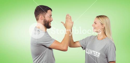 Composite image of smiling volunteer doing high five in office