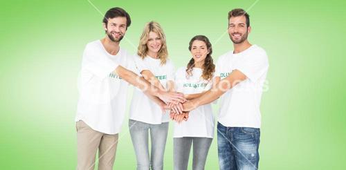 Composite image of group portrait of happy volunteers with hands together