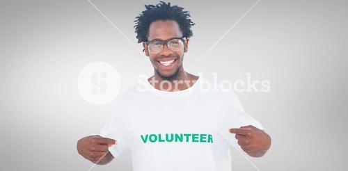 Composite image of handsome man pointing to his volunteer tshirt