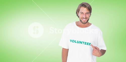 Composite image of smiling man pointing to his volunteer tshirt