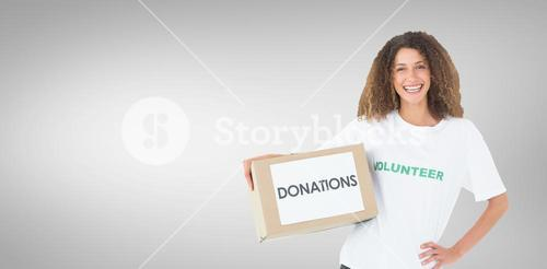 Composite image of smiling volunteer holding a box of donations with hand on hip