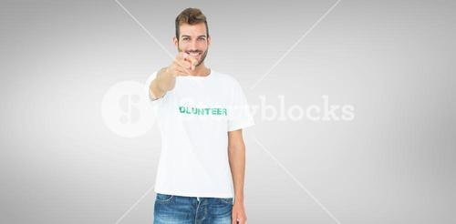 Composite image of portrait of a happy male volunteer pointing at you