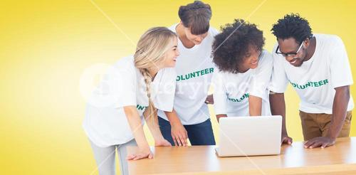 Composite image of smiling volunteers working together on a laptop