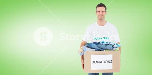 Composite image of attractive man holding donation box with clothes
