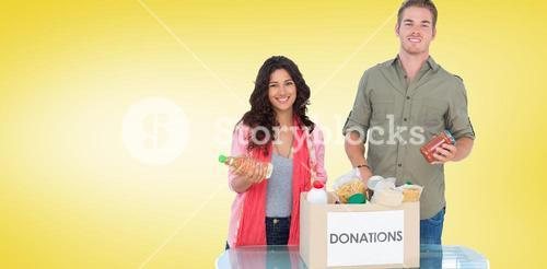 Composite image of smiling volunteers taking out food from donations box