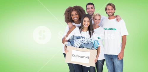 Composite image of smiling group of volunteers holding donation box