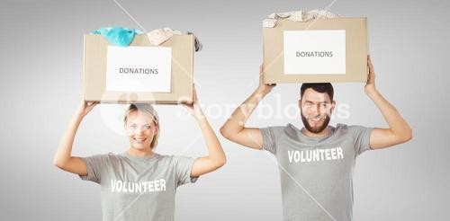 Composite image of portrait of volunteers carrying donation boxes on head