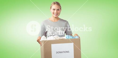Composite image of portrait of beautiful woman holding clothes donation box