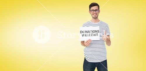 Composite image of man holding a donation welcome note while gesturing thumbs up
