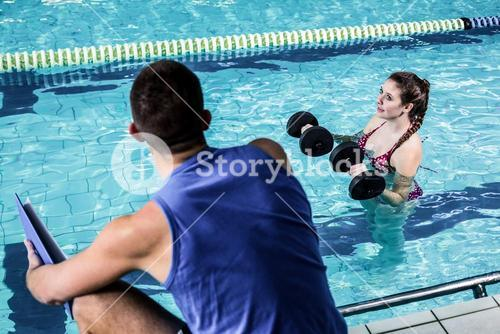Smiling fit woman doing aqua aerobics