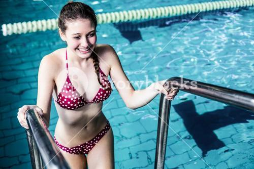 Smiling woman getting out the pool
