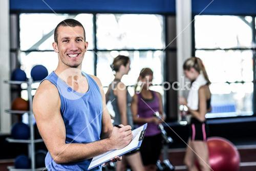 Muscular trainer writing on clipboard