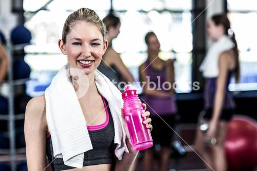 Smiling woman with bottle of water posing