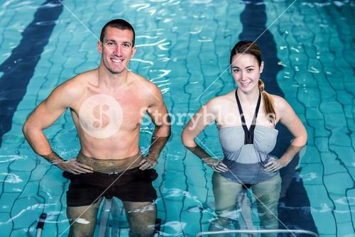 Smiling couple doing aqua aerobics