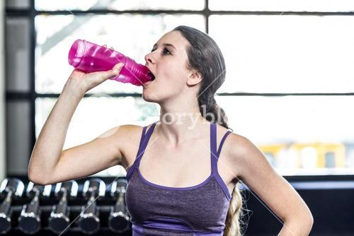 Thirsty woman drinking water on exercise ball