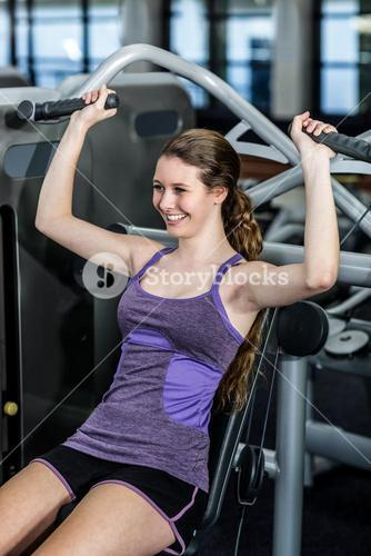 Fit woman using exercise machine