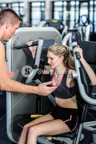 Trainer motivating woman while using exercise machine
