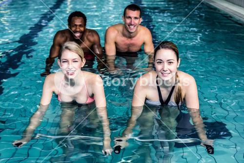 Fit smiling group pedaling on swimming bike